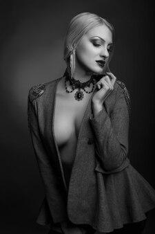 Stijlvol zwart-wit studioportret van een geweldige vrouw met lichte make-up draagt een jas op een naakt lichaam