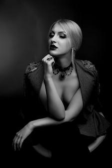 Stijlvol zwart-wit studioportret van een mooie vrouw met lichte make-up draagt een jas op een naakt lichaam
