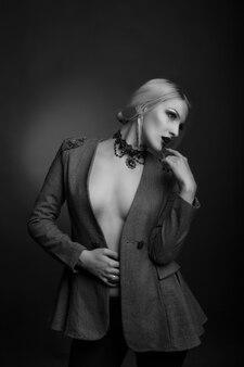 Stijlvol zwart-wit studioportret van een prachtige vrouw met lichte make-up draagt een jas op een naakt lichaam