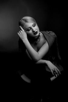 Stijlvol zwart-wit studioportret van een sensuele vrouw met lichte make-up draagt een jas op een naakt lichaam