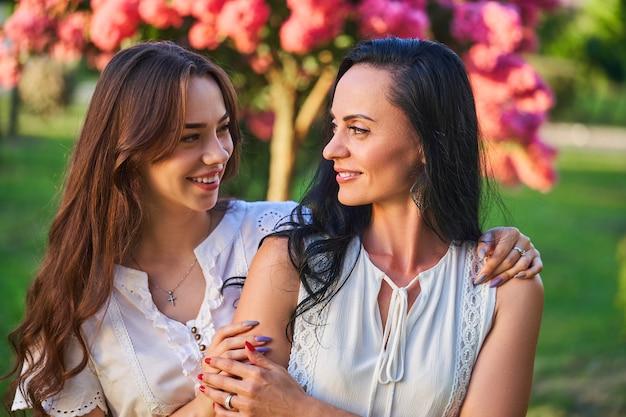 Stijlvolle aantrekkelijke glimlachende blije gelukkige moeder en dochter knuffelen in een park buiten