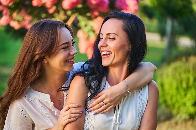 Stijlvolle aantrekkelijke glimlachende vrolijke gelukkige moeder en dochter omhelzen en hebben samen plezier in een park buiten