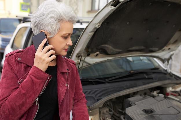 Stijlvolle aantrekkelijke grijze haren rijpe vrouwelijke bestuurder permanent in de buurt van haar gebroken witte auto met open kap en praten aan de telefoon