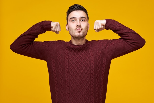 Stijlvolle aantrekkelijke jonge bebaarde man in gebreide knusse trui kracht tonen, handen opsteken, vuisten gebald houden, zelfverzekerd en trots op zichzelf voelen. vertrouwen en machtsconcept