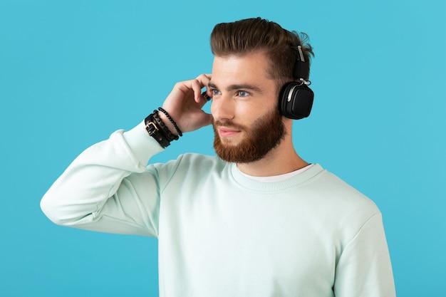 Stijlvolle aantrekkelijke jonge bebaarde man luisteren naar muziek op draadloze koptelefoon moderne stijl zelfverzekerde stemming geïsoleerd op blauwe muur