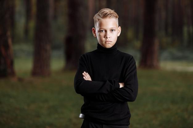 Stijlvolle aantrekkelijke jonge kerel met een modieus kapsel in een trendy zwarte outfit geniet van een buitenvakantie in het park.