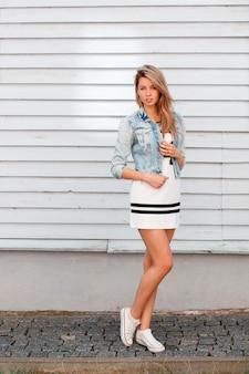 Stijlvolle aantrekkelijke jonge vrouw in een sportieve jurk met een patroon in een stijlvolle denim jasje in witte sneakers poseren in de buurt van een houten witte muur op straat. amerikaans schattig meisje op een wandeling op een zomerdag.