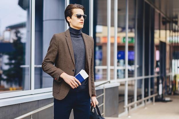 Stijlvolle aantrekkelijke kerel in jasje met paspoort en kaartjes