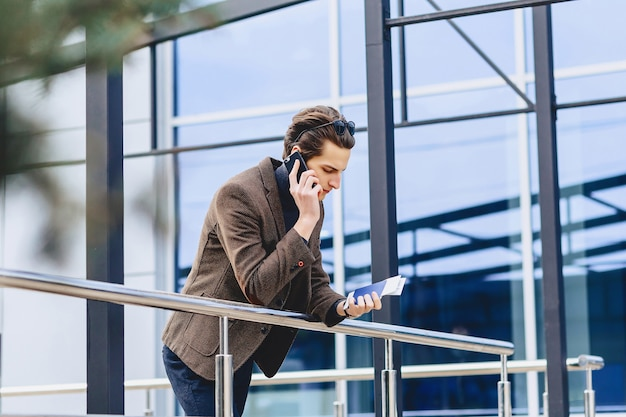 Stijlvolle aantrekkelijke kerel in jasje met telefoonpaspoort en kaartjes
