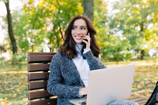 Stijlvolle aantrekkelijke onderneemster in grijze pullover die aan de telefoon spreekt en op laptop buiten werkt. ze heeft kort donker haar en grote blauwe ogen, zijwaarts kijkend