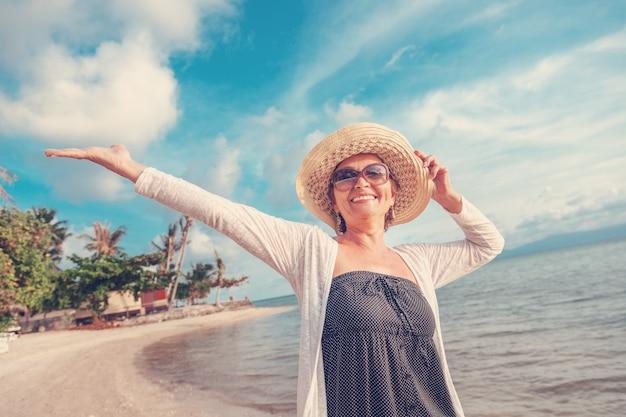 Stijlvolle aantrekkelijke volwassen vrouw 50-60 met open armen aan de kust, reizen en pensioen, mode en schoonheid, actieve ouderen