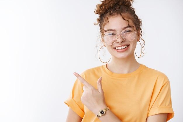 Stijlvolle aantrekkelijke zorgeloze roodharige tiener vrouwelijke college student plezier glimlachend in het algemeen genieten van feest show meisjes heersen wereld rock-n-roll gebaar grijnzend trendy bril oranje t-shirt