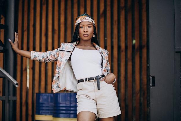 Stijlvolle afrikaanse amerikaanse vrouw in het park op de houten achtergrond