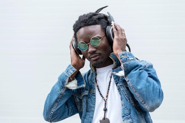 Stijlvolle afrikaanse man in spijkerbroek met dreadlocks en zonnebril luistert naar muziek in de koptelefoon op een wit