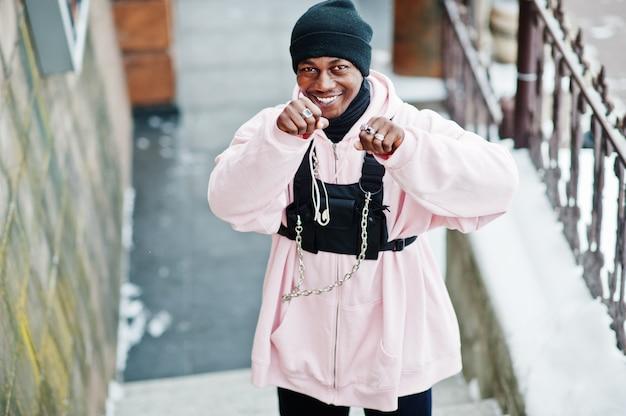 Stijlvolle afrikaanse stijl afro-amerikaanse man in roze hoodie gesteld op winterdag en boksen handen.
