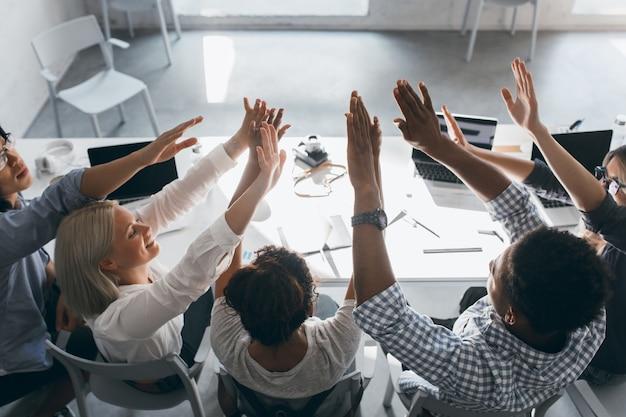 Stijlvolle afrikaanse student in polshorloge handen slaan met vrienden, zittend in de buurt van computer. portret van de achterkant van vrolijke kantoormedewerkers die tijdens de werkdag voor de gek houden en grappen maken.