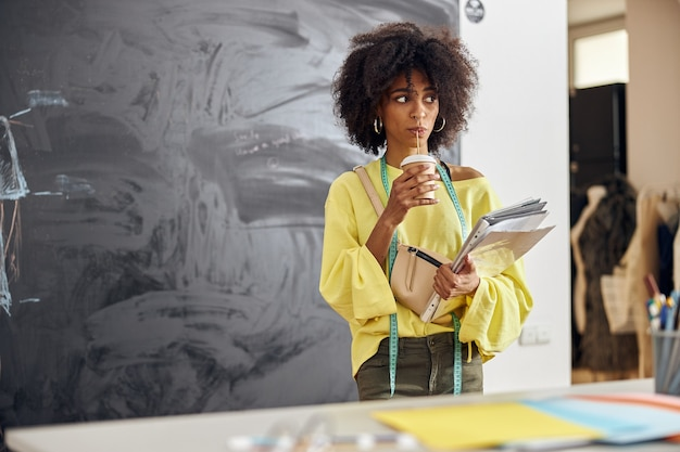 Stijlvolle afro-amerikaanse designer drinkt drank aan tafel in de buurt van schoolbord tijdens naailes