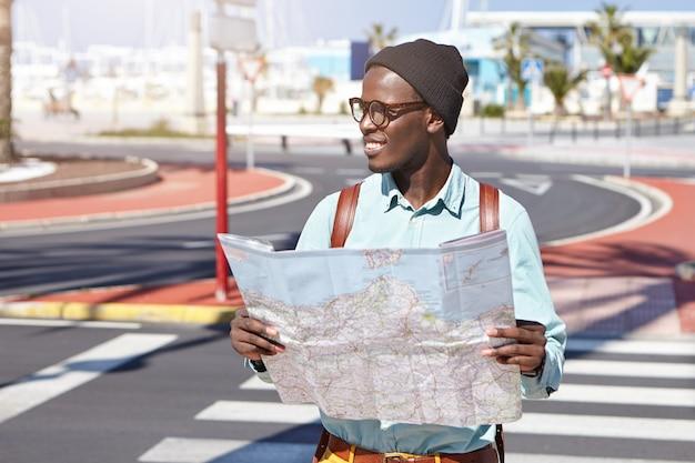 Stijlvolle afro-amerikaanse man op straat met kaart
