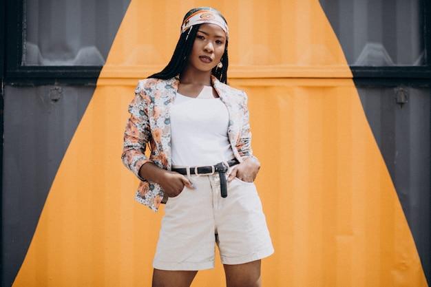 Stijlvolle afro-amerikaanse vrouw door de gekleurde muur