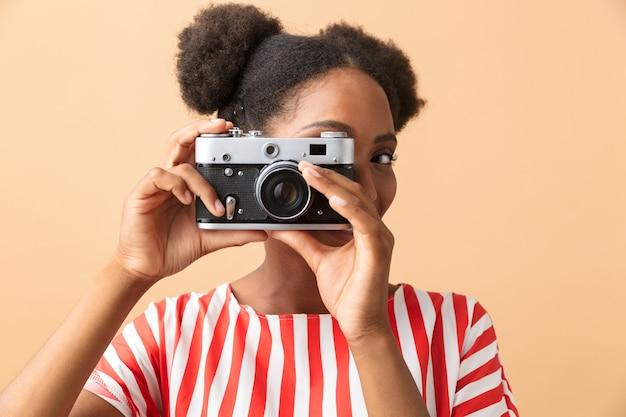 Stijlvolle afro-amerikaanse vrouw glimlachend en fotograferen op retro camera, geïsoleerd