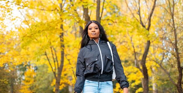Stijlvolle afro-amerikaanse vrouw in trendy vrijetijdskleding buitenshuis tegen een achtergrond van felgeel herfstgebladerte