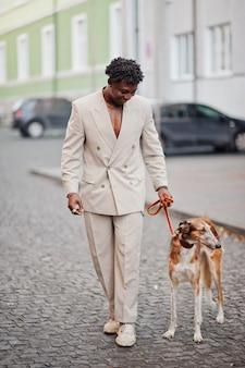 Stijlvolle afro man in beige old school pak met russische borzoi hond. modieuze jonge afrikaanse man in casual jas op blote romp.