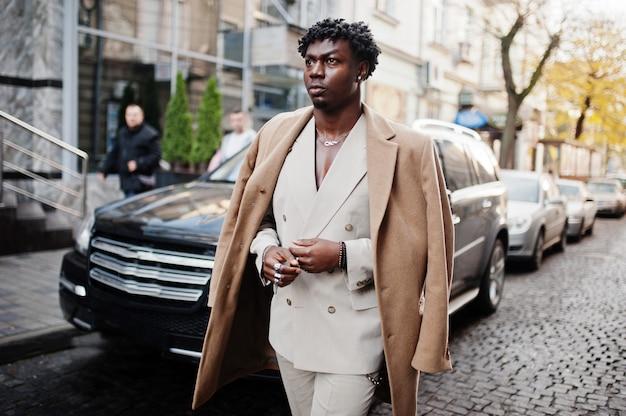 Stijlvolle afro man in beige oude school pak en jas lopen tegen zwarte zakelijke auto. modieuze jonge afrikaanse man in casual jas op blote romp.