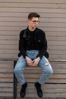 Stijlvolle amerikaanse man in casual fashion denim kleding in lederen stijlvolle zwarte sneakers black