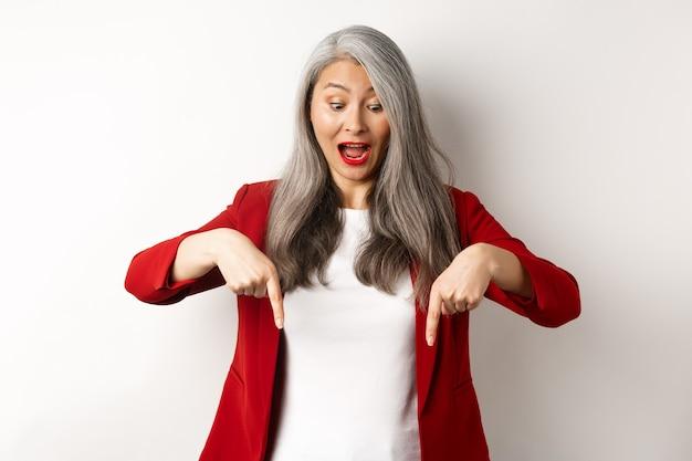 Stijlvolle aziatische oudere vrouw in rode blazer die speciale promotie bekijkt, vingers naar beneden wijst en opgewonden kijkt, schreeuw van vreugde, witte muur.