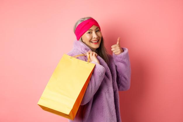Stijlvolle aziatische senior vrouw gaat winkelen, draagt een papieren zak op de schouder en toont duim-omhoog, winkelkortingen op roze aanbevelen.