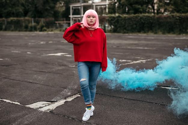 Stijlvolle aziatische tiener die zich voor blauwe rook bevindt