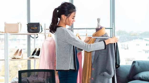 Stijlvolle aziatische vrouw mode-ontwerper en kleermaker werken in kleding winkel
