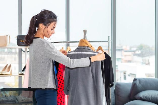 Stijlvolle aziatische vrouw mode-ontwerper en kleermaker werken in kleding winkel.