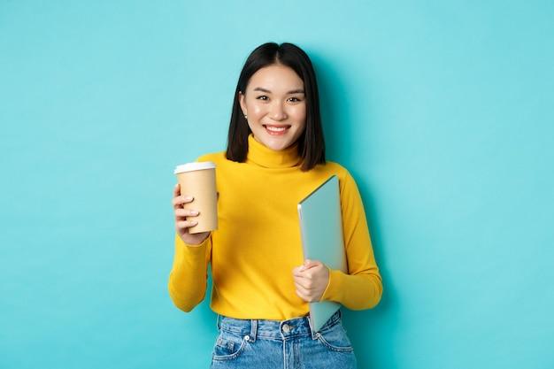 Stijlvolle aziatische vrouwelijke student met kopje koffie permanent over blauwe achtergrond, laptop in de hand houden, glimlachend in de camera, permanent over blauwe achtergrond.