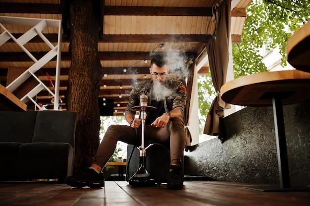 Stijlvolle baard man in glazen en militaire jas roken waterpijp op straat bar
