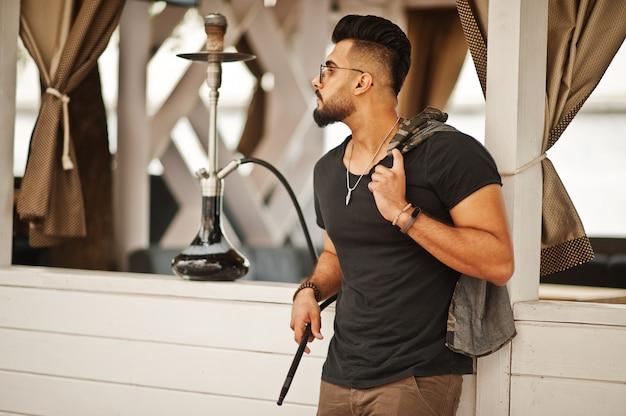 Stijlvolle baard man in glazen en zwart t-shirt roken waterpijp buiten