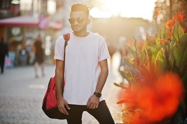 Stijlvolle baard man op roze t-shirt, zonnebril en rugzak india model poseerde buiten op straat van zonsondergang stad