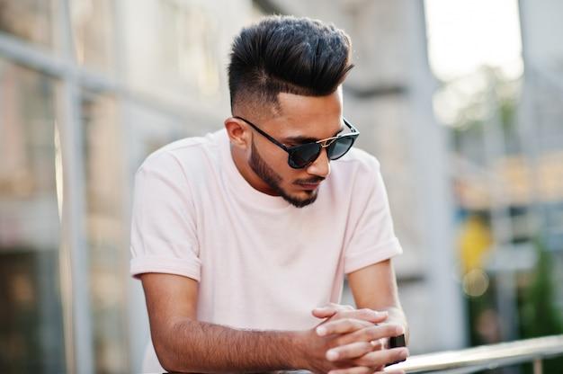 Stijlvolle baard man op zonnebril en roze t-shirt india model poseerde buiten op straat van de stad