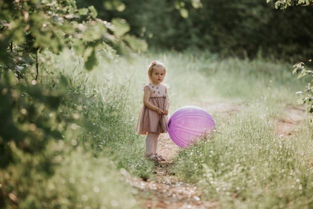 Stijlvolle baby meisje 2-5 jaar oud bedrijf grote ballon trendy roze jurk in weide dragen. speels. klein meisje met een ballon in het park. verjaardagsfeest.