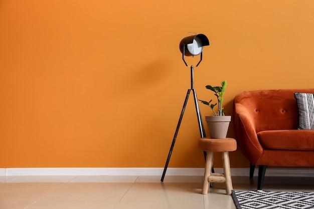 Stijlvolle bank met lamp en kamerplant bij kleurmuur in kamer