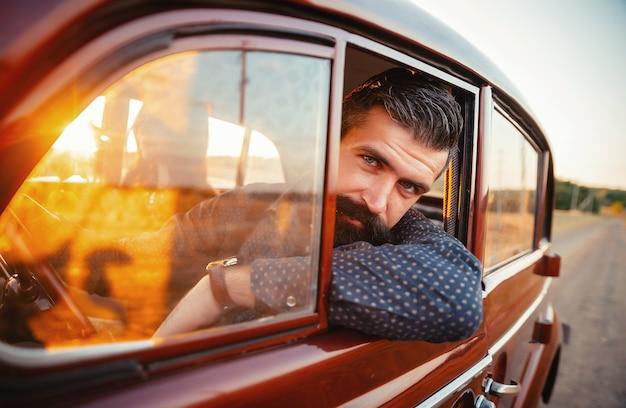 Stijlvolle bebaarde brunette met een snor in een shirt en broek met bretels gluurt uit de cabine van een oude vintage bruine auto op de achtergrond van een landelijke weg