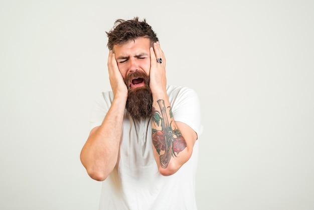 Stijlvolle bebaarde man huilen. ongelukkige hipster man man met tatoeage, huilen en depressief zijn.