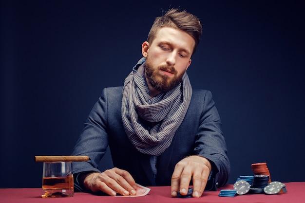 Stijlvolle bebaarde man in pak en sjaal spelen in donkere casino een sigaar roken en whisky drinken