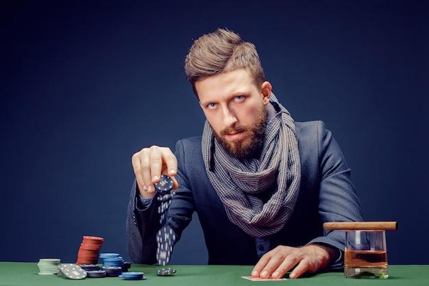 Stijlvolle bebaarde man in pak en sjaal spelen in donkere casino