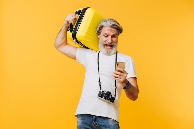 Stijlvolle bebaarde man lachen, met een gele koffer en kijken naar de telefoon die een land kiest om te reizen.