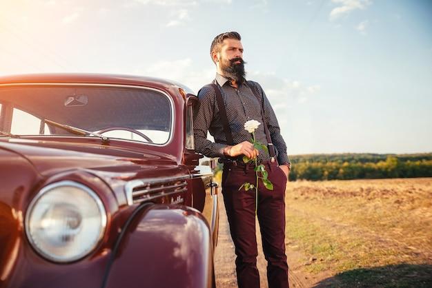 Stijlvolle bebaarde man met een snor in klassieke broek met bretels en een donker shirt met een roos in zijn handen bij een bruine retro auto