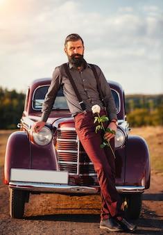 Stijlvolle bebaarde man met snor in klassieke broek met bretels en donker shirt met witte roos
