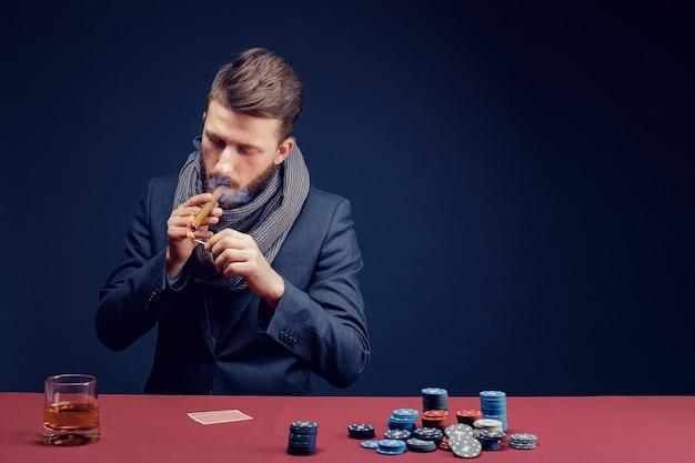 Stijlvolle bebaarde man spelen in donkere casino een sigaar roken