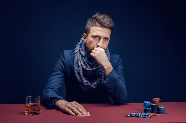 Stijlvolle bebaarde man spelen in donkere casino en whisky drinken