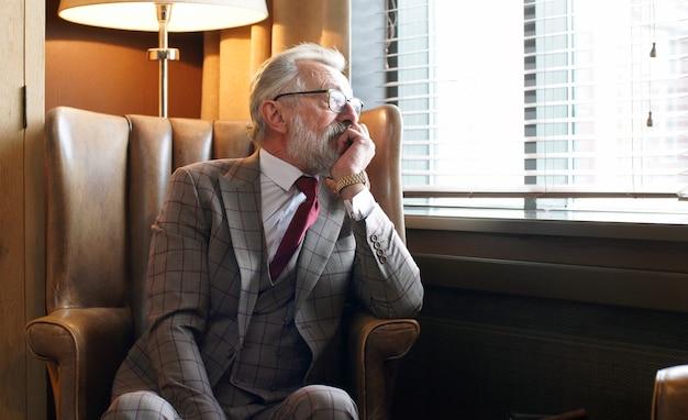Stijlvolle, bedachtzame, grijsharige man in pak en bril zit op een stoel bij het raam
